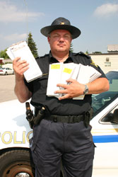 OPP Sergeant Cam Wooley with books of traditional paper traffic tickets