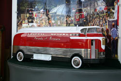 A scale model of the Futurliner sits within the real one. Both front and rear axles use dual wheels.