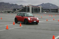 A Mini rounds a sharp turn with one tire flattened, but keeps its grip