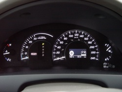 The gauge cluster consists of (L to R) a small coolant temperature gauge, instant fuel consumption gauge with inset transmission gear indicator and Ready light, speedometer, and fuel gauge.  The instant fuel consumption gauge includes a blue 'E mode' indicating when the car is running on battery power alone.