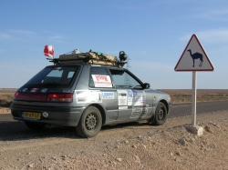 Mazda parked next to a Camel crossing sign in Western Sahara