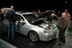 Automotive journalists pore over a vehicle at the Toronto Auto Show