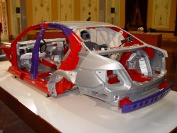 Stripped of its body panels, this C-Class body structure shows the deformation points and crash resistant structures designed to absorb frontal and side impacts. This photo also shows the inflated curtain airbags and driver\'s knee airbag.
