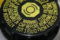 Brake fluid reservoir cap indicating required fluid type